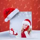 happy festive blonde with gift against orange reindeer pattern