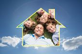 Happy family lying on the grass in a circle against cloudy sky with sunshine