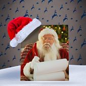 Santa claus writing his list with a quill against grey reindeer pattern