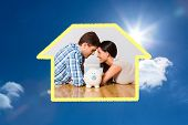 Young couple lying on floor smiling with piggy bank against bright blue sky with clouds