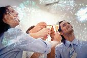 Cheerful business team toasting with Champagne against colourful fireworks exploding on black background