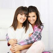 Beautiful girls twins in pajamas at home