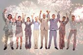 Happy business team raising their arms against colourful fireworks exploding on black background