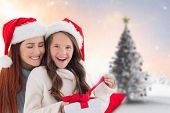 Mother and daughter opening gift against blurry christmas scene