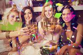 stock photo of champagne color  - Pretty friends drinking champagne together against flying colours - JPG