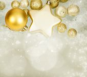 Golden Christmas balls and star on sparkling holiday background