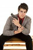 Man In Sweater Holding Gun Sitting Looking