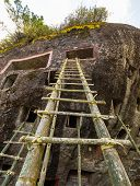 foto of coffin  - Open graves in a cliff with bamboo stairs for access during the ceremony of cleaning corpses  - JPG