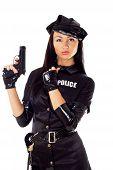 stock photo of cap gun  - Portret of beautiful sexy policewoman with handcuffs in a black uniform that aiming a gun - JPG