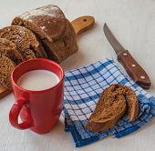 Sliced Rye Bread Tabatière On A Cutting Board And  Red Cup With Milk On The Table