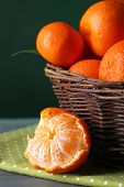 Fresh ripe mandarins in wicker basket, on wooden  table, on color background