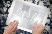 2015 against hands touching tablet screen