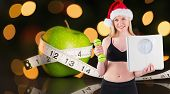 Festive fit blonde smiling at camera against measuring tape