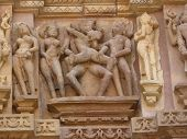 stock photo of kandariya mahadeva temple  - Sculptures of loving couples illustrating the Kama Sutra on walls of Kandariya Mahadeva Temple at Khajuraho in India Asia - JPG