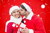 Festive young couple holding gift against red background