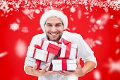 Festive man holding christmas gifts against red background