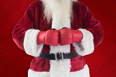 Santa Claus wears boxing gloves against red background