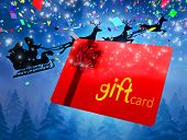 Santa flying his sleigh behind gift card against snow falling on fir tree forest