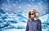 Portrait of beautiful model in winter mountains wearing stylish sunglasses and fashionable coat with fur on the hood enjoying snowfall, wintertime vacation concept