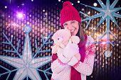 Cute brunette in warm clothing hugging teddy bear against digitally generated cool nightlife background
