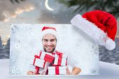 stock photo of north-pole  - festive man holding christmas gifts against cute christmas village at north pole - JPG