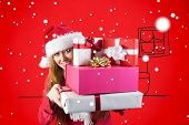 Festive redhead holding pile of gifts against red background