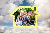Cute family enjoying a picnic against blue sky with white clouds