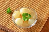bowl of pickled onions and parsley on bamboo place mat