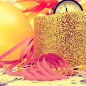 golden balloons, golden top hat, streamers and confetti for the new years party, with a retro effect
