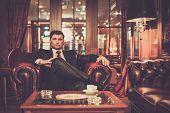 Confident handsome brunette sitting in luxury interior