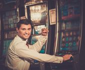 Handsome happy brunette man in white shirt near slot machine