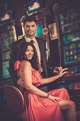 Beautiful couple near slot machine in a casino