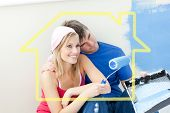 Affectionate couple painting a room against house outline