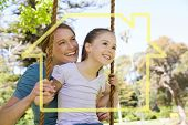 House outline against happy mother swinging daughter at park