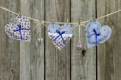 Floral fabric hearts and heart-shaped locks hanging on clothesline by rustic wooden fence