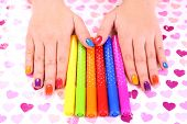 Multicolor female manicure with markers on bright background