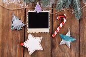 Blank photo frames and Christmas decor with snow fir tree on wooden table background