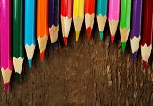 Colorful pencils on rustic wooden background