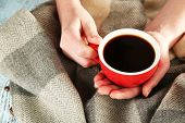 Cup of coffee in hands on plaid background
