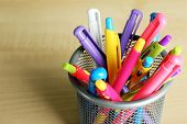 Metal holder with different pens on wooden background