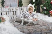 Child Sledding In Yard Of Winter Snow