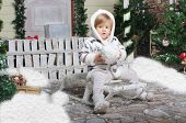 Child Sits On Sled With Snow In Hands