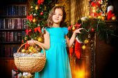 Cute seven year old girl stands with a gift by the Christmas tree at home. The magic of Christmas.