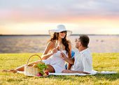 love, dating, people and holidays concept - happy couple drinking champagne on picnic over seaside sunset background