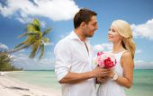 holidays, travel, tourism, people and dating concept - happy couple with bunch of flowers over tropical beach background