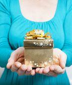 Woman hands holding golden gift box