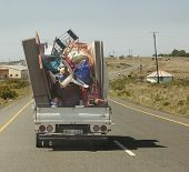 Truck driving down highway with a very dangerous load that was not safely tied down.
