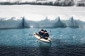 stock photo of canoe boat man  - Two men in a canoe among icebergs in Antarctica - JPG