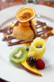 Ice-cream dessert with fruits in plate, close-up