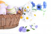 stock photo of wildflowers  - wooden basket of easter eggs with wildflowers - JPG